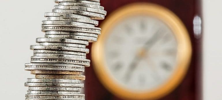 A stack of coins with a clock on the wall behind it