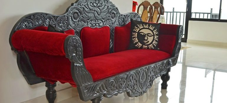 An elaborately decorated couch with red cushioning