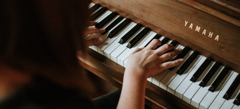 Woman playing a piano after moving it with the help of piano movers Philadelphia