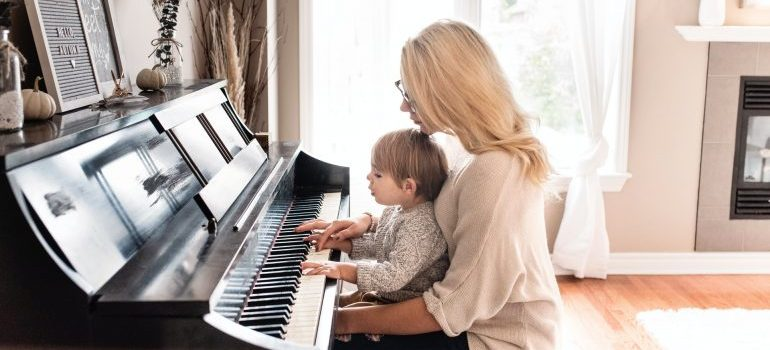 Woman and a child playing a piano