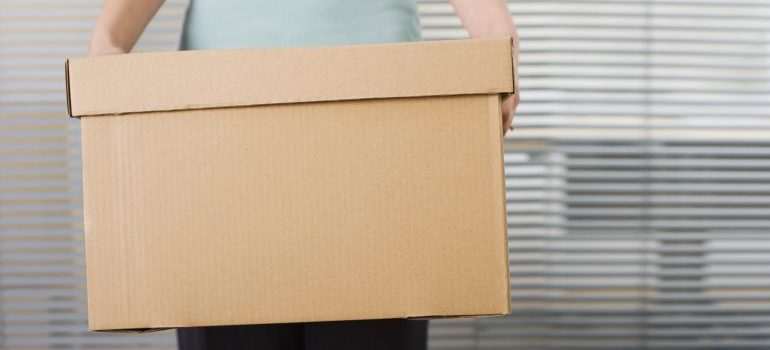 Woman holding box to store, representing storage units Philadelphia
