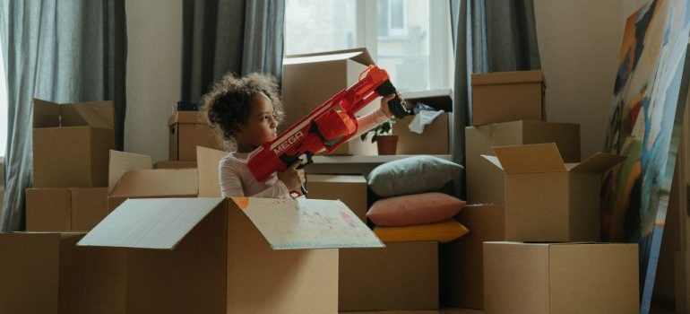Girl playing in empty moving boxes