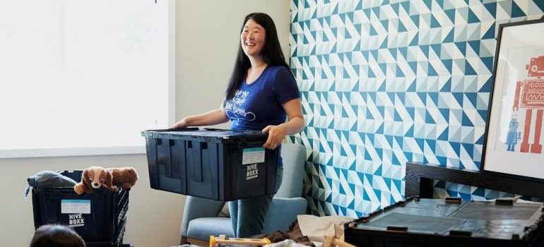 A woman using a plastic moving box
