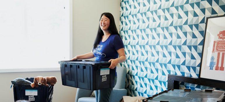 A woman using a plastic moving bin