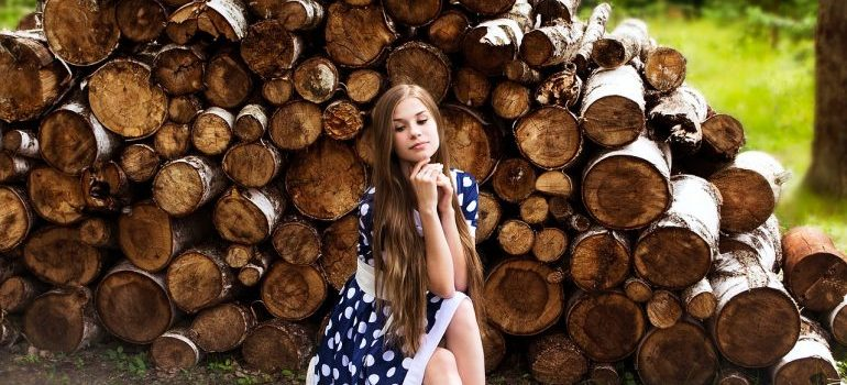 a girl sitting in front of pile of firewood