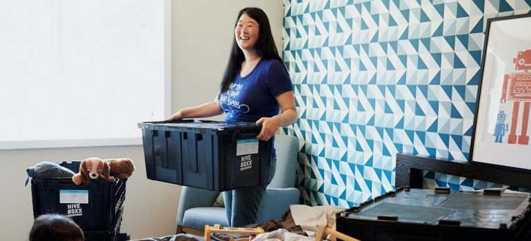 Happy mother using reusable boxes for moving with her family