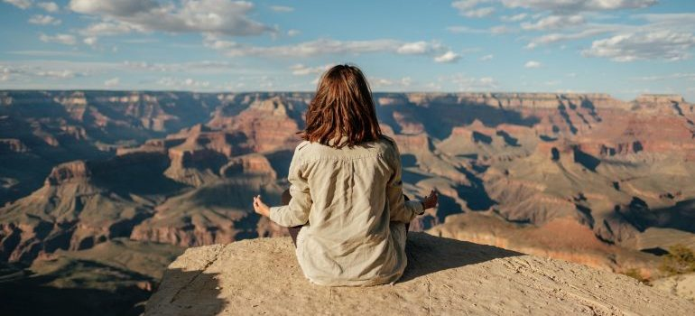 A women meditating on a cliff