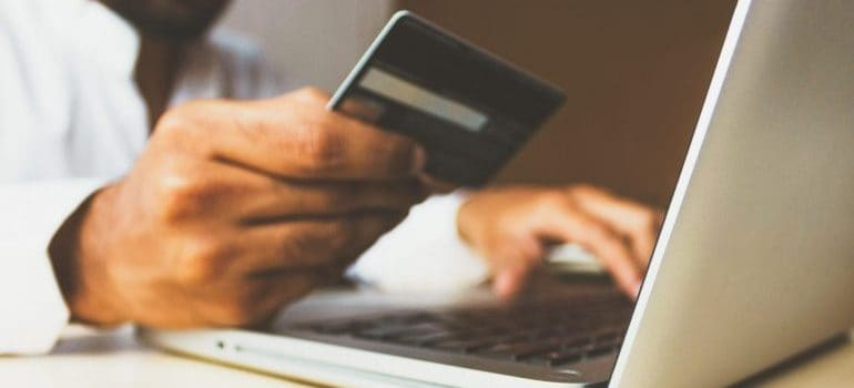 Man using his bank card to shop online on his laptop