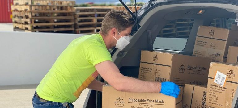 A man with gloves and face masks storing boxes in a vehicle.