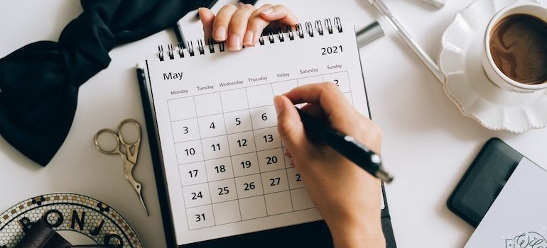 person writing in a paper calendar