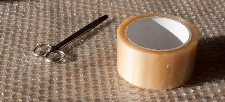 Duck tape and scissors placed on a bubble wrap.
