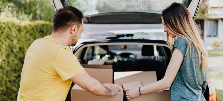 Man and woman putting cardboard boxes in car.