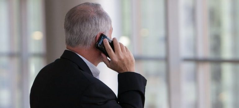 A man on a phone trying to hire professional packers for moving your art collection