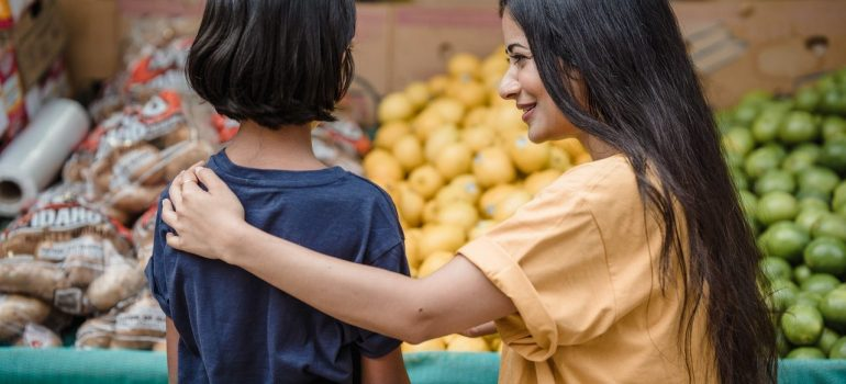 a mother buying produce with her child