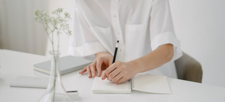 a woman in a white shirt writing down her plans in a notebook