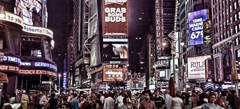 a crowd of people walking on Times Square with billboards above them