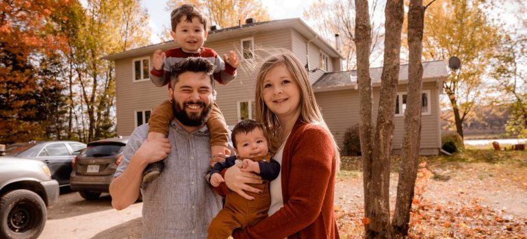 two parents posing with two of their children in front of their suburb home