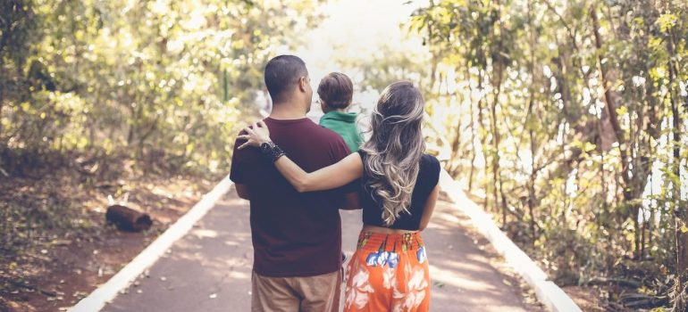 a young family walking down the road through the forest